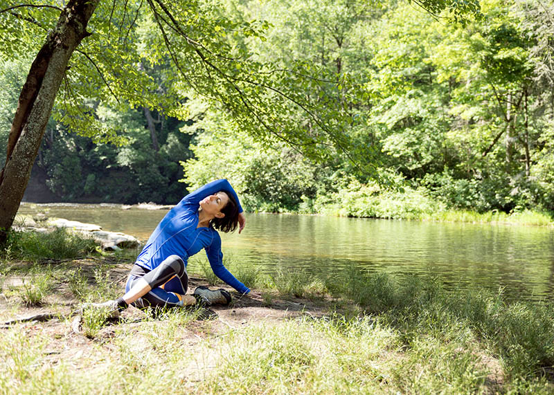 woman doing yoga by a stream