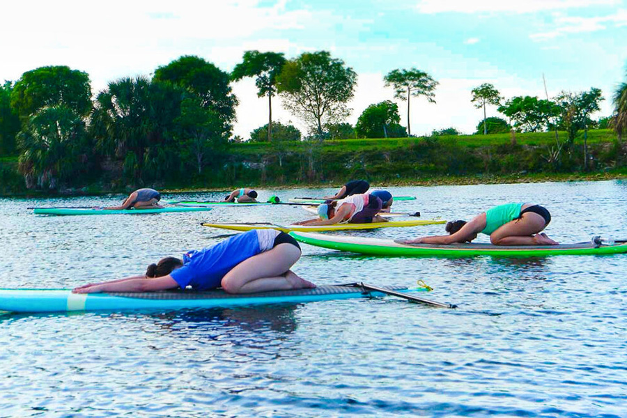 students doing child's pose on paddle boards in the water
